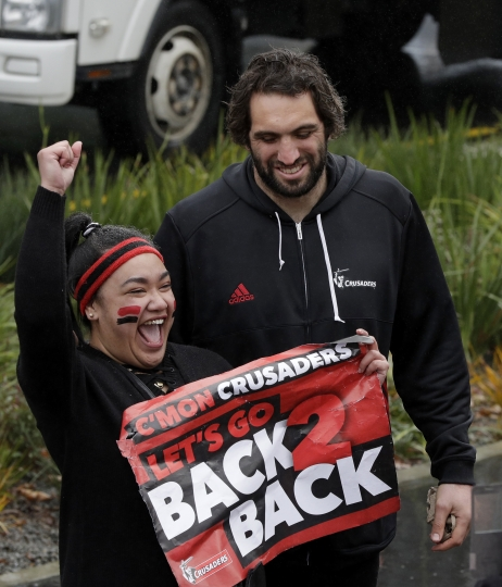 All Black and Crusaders second row forward Sam Whitelock poses for a photo with a supporter during a victory parade through the central business district after winning the 2018 Super Rugby title in Christchurch, New Zealand, Monday, Aug. 6, 2018. The Crusaders defeated the Lions 37-18 in Saturday's Aug. 4, final. (AP Photo/Mark Baker)