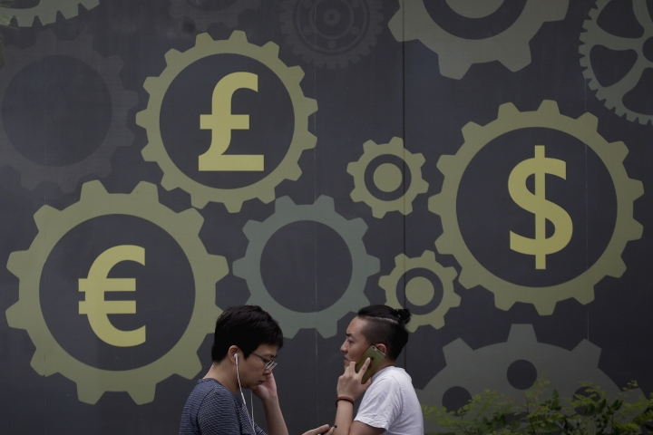Chinese people walk by a mural displaying world currency symbols on display outside a bank in Beijing, Monday, Aug. 6, 2018. China has tightened controls on trading in its yuan to discourage speculators after a decline against the dollar amid a tariff dispute with Washington fueled fears of a damaging outflow of capital from the world's second-largest economy. (AP Photo/Andy Wong)