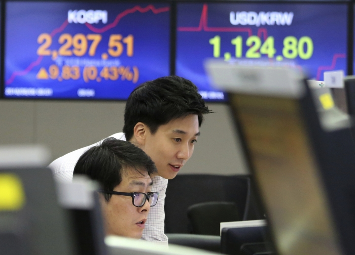 Currency traders watch monitors at the foreign exchange dealing room of the KEB Hana Bank headquarters in Seoul, South Korea, Monday, Aug. 6, 2018. Asian stocks rose Monday despite a new Chinese threat of tariff hikes on U.S. goods after Washington reported solid employment numbers. (AP Photo/Ahn Young-joon)