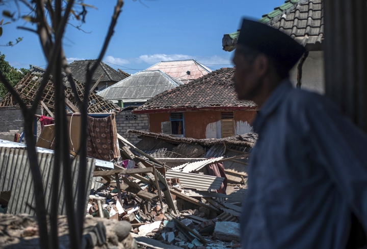 An Indonesian man inspects the damage in a village from a major earthquake in Kayangan on Lombok Island, Indonesia, Monday, Aug. 6, 2018. Indonesian authorities said Monday that rescuers still haven't reached some devastated parts of the tourist island of Lombok after the powerful earthquake flattened houses and toppled bridges, killing large number of people and shaking neighboring Bali. (AP Photo/Fauzy Chaniago)