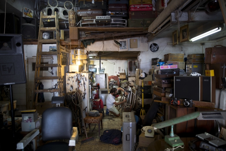 In this Thursday, July 26, 2018 photo, an Israeli shop keeper works on a bicycle in his antique store at the flea market in Jaffa, Israel. Israel's port city of Jaffa is an ancient place. Today glass towers and modern apartment complexes rise amid Jaffa's old white stone buildings. It's famous for its flea market and hummus cafes. But visitors will also find trendy bars, galleries and boutiques. (AP Photo/Oded Balilty)