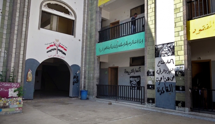 "The black al-Qaida flag and the slogan in Arabic ""al-Qaida passed here,"" on the right wall, are sprayed on a damaged school that was turned into a religious court in the southern city of Taiz, Yemen, in this Oct. 16, 2017 photo. Coalition-backed militias have enlisted al-Qaida fighters to battle the Shiite rebels known as Houthis who have besieged Taiz for more than two years. (AP Photo)"