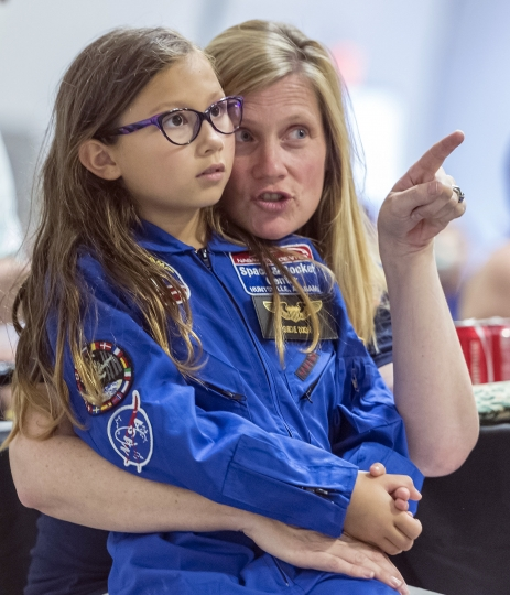 In this July 13, 2018 photo, Meredith Dixon points out interesting visuals to her daughter Birdie, a Space Camp participant, as they listen to a talk on space flight from NASA astronaut Dottie Metcalf-Lindenburger, at the U.S. Space & Rocket Center in Huntsville, Ala. Huntsville's tourism industry is rooted in the U.S. space program and its critical, ongoing research into getting astronauts back to the moon and on to Mars. (AP Photo/Vasha Hunt)
