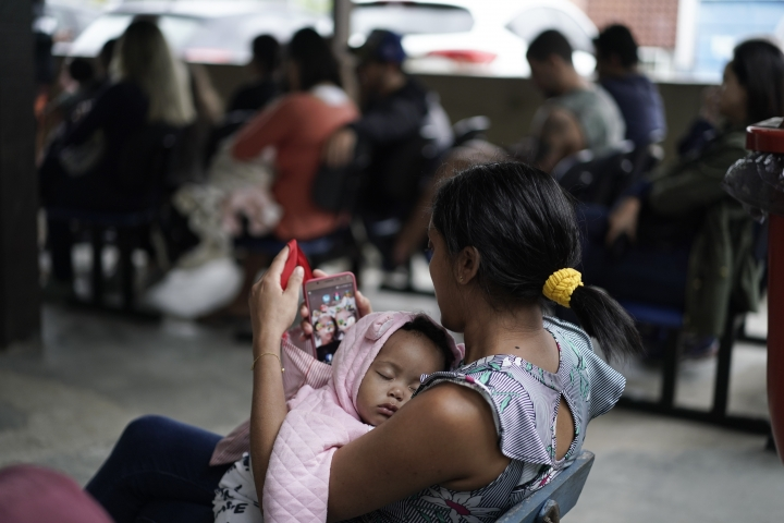 A mother cradles her baby as they wait to receive a vaccine against polio in Rio de Janeiro, Brazil, Monday, Aug. 6, 2018. Brazilian health authorities launch a nationwide vaccination campaign against measles and polio, two diseases that are showing up in larger numbers in Latin America's largest nation after being all but eradicated. (AP Photo/Leo Correa)