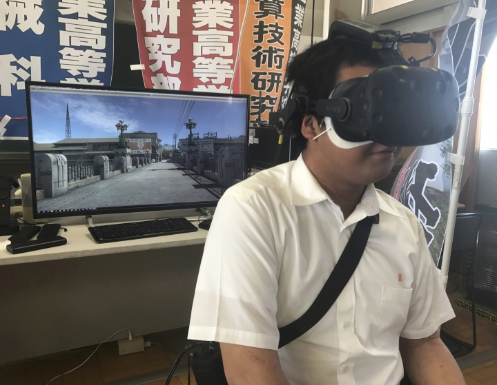 In Friday, Aug. 8, 2018, photo, Namio Matsura, a 17-year-old member of the computation skill research club at Fukuyama Technical High School, watches the bridge over the Motoyasu River, seen on screen, before atomic bomb fell on Hiroshima in virtual reality experience at the school in Hiroshima, western Japan. Over two years, the group of Japanese high school students has been painstakingly producing a five-minute virtual reality experience that recreates the sights and sounds of Hiroshima before, during and after the U.S. dropped an atomic bomb on the city 73 years ago. (AP Photo/Haruka Nuga)
