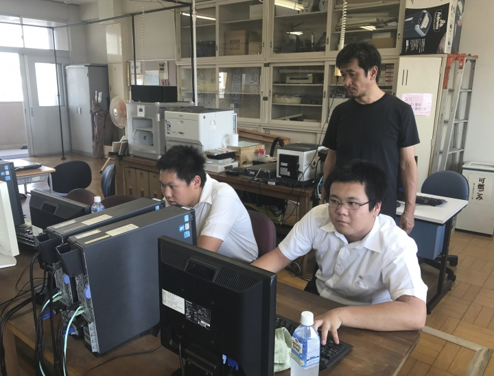 In Friday, Aug. 8, 2018, photo, Katsushi Hasegawa, standing, a computer teacher, watches members of the computation skill research club at Fukuyama Technical High School work on computer graphic software at the school in Hiroshima, western Japan. Over two years, the group of Japanese high school students has been painstakingly producing a five-minute virtual reality experience that recreates the sights and sounds of Hiroshima before, during and after the U.S. dropped an atomic bomb on the city 73 years ago. (AP Photo/Haruka Nuga)