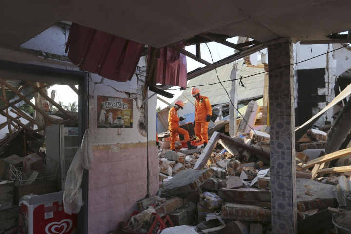 Rescue teams search for victims in the rubble caused by an earthquake in North Lombok, Indonesia, Monday, Aug. 6, 2018. The powerful earthquake struck the Indonesian tourist island of Lombok, killing a number of people and shaking neighboring Bali, as authorities on Monday said thousands of houses were damaged and the death toll could climb. (AP Photo/Tatan Syuflana)