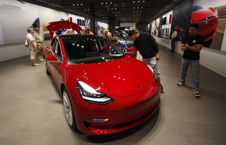 """In this Friday, July 6, 2018, photograph, prospective customers confer with sales associates as a Model 3 sits on display in a Tesla showroom in the Cherry Creek Mall in Denver. The Insurance Institute for Highway Safety, in a paper titled """"Reality Check,"""" issued the warning Tuesday, Aug. 7, 2018, after testing five of the systems from Tesla, Mercedes, BMW and Volvo on a track and public roads. The systems tested, in the Tesla Model 3 and Model S, BMW's 5-Series, the Volvo S-90 and the Mercedes E-Class, are among the best in the business right now and have been rated """"superior"""" in previous IIHS tests. David Zuby, the institute's chief research officer, said the systems do increase safety but the tests show they are not 100 percent reliable. (AP Photo/David Zalubowski)"""