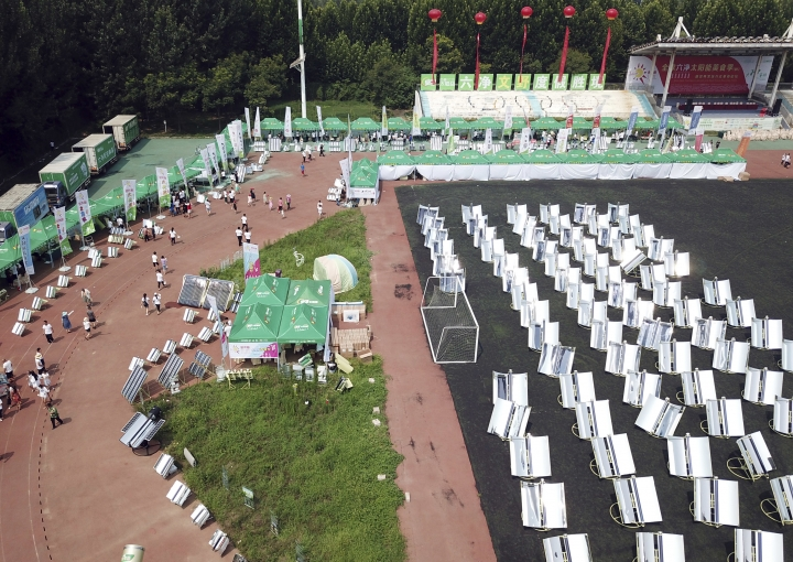 In this photo taken Thursday, Aug. 2, 2018, rows of solar cookers which use reflective mirrors to heat metal and glass vacuum tubes up to 400°C (275°F) to cook food during a solar food festival in Dezhou in the eastern Shandong province in China. China is the world's biggest consumer and producer of solar technologies. Many homes outside the biggest cities are equipped with solar panels to heat water for bathing. But roughly 600 million of China's 1.4 billion people still cook with sooty burning coal, wood or other biomass, causing health and environmental problems including contributing to climate change. (AP Photo/Sam McNeil)