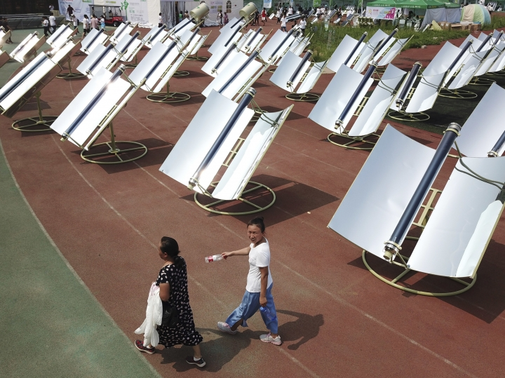 In this photo taken Thursday, Aug. 2, 2018, women walk past rows of solar cookers which use reflective mirrors to heat metal and glass vacuum tubes up to 400°C (275°F) to cook food during a solar food festival in Dezhou in the eastern Shandong province in China. China is the world's biggest consumer and producer of solar technologies. Many homes outside the biggest cities are equipped with solar panels to heat water for bathing. But roughly 600 million of China's 1.4 billion people still cook with sooty burning coal, wood or other biomass, causing health and environmental problems including contributing to climate change. (AP Photo/Sam McNeil)