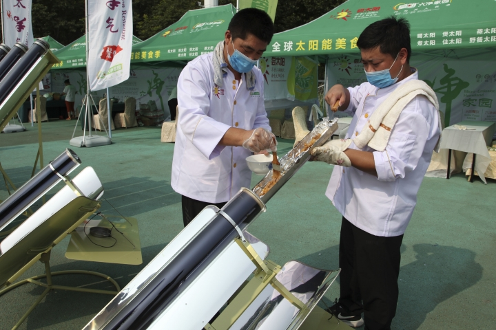 In this photo taken Thursday, Aug. 2, 2018, chefs prepare to cook skewers of meat in a solar cooker using a metal and glass vacuum tube heated by mirrors curved to capture the sun's heat in Dezhou in the eastern Shandong province in China. Two dozen chefs with white aprons and hats cooked soups, baked buns, potatoes, and boiled rice at a festival to demonstrate the potential of solar cookers that organizers claim can help reduce climate-changing greenhouse gas emissions. (AP Photo/Fu Ting)