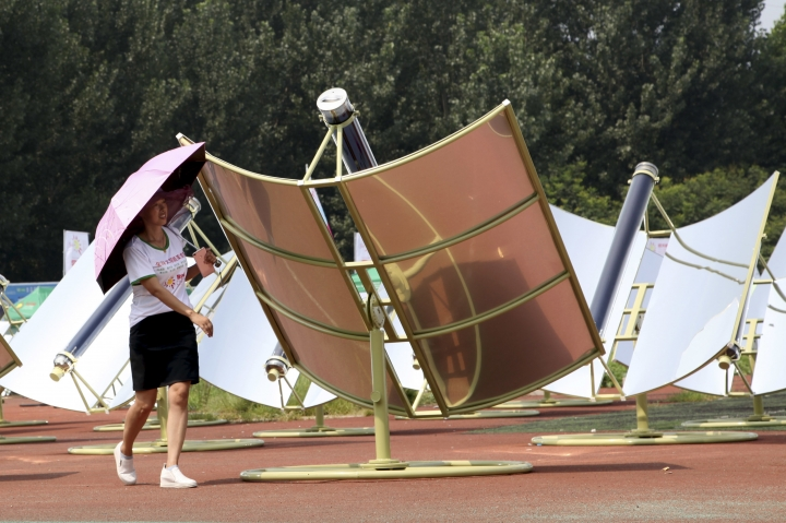 In this Thursday, Aug. 2, 2018, photo, a woman rotates a solar cooker, a device using a metal and glass vacuum tube heated by mirrors curved to capture the sun's heat, to face the sun in Dezhou in the eastern Shandong province in China. Two dozen chefs with white aprons and hats cooked soups, baked buns, potatoes, and boiled rice at a festival to demonstrate the potential of solar cookers that organizers claim can help reduce climate-changing greenhouse gas emissions. (AP Photo/Fu Ting)