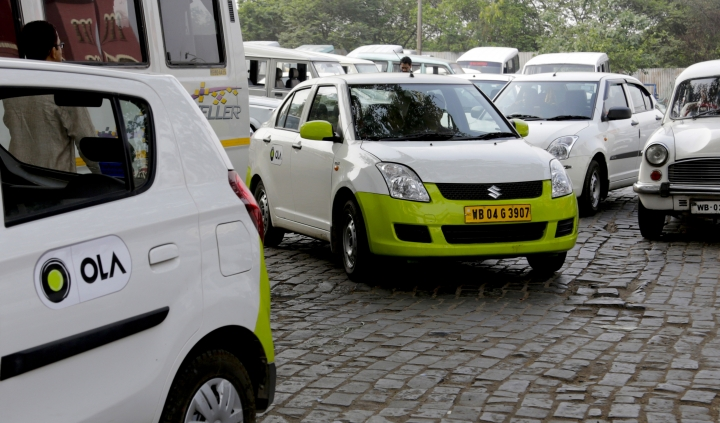 FILE - In this file photo dated March 29, 2016, Ola cabs wait for customers in Kolkata, India. In a company announcement issued Tuesday Aug. 7, 2018, Indian ride-hailing service Ola said it plans to launch in the U.K., following its launch in Australia. (AP Photo/ Bikas Das, FILE)