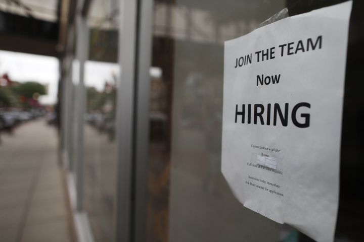 """In this Wednesday, July 18, 2018, photograph, a """"now hiring"""" sign hangs in the window of a Chinese restaurant in downtown Fargo, N.D. Data shows that small businesses are hiring less, despite the strong economy, partly because they are losing employees to bigger firms. (AP Photo/David Zalubowski)"""