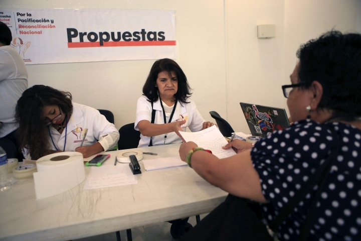 Volunteers collect suggestions from people attending the first in a series of meetings with Mexico's President-elect Andres Manuel Lopez Obrador that will be held across the country over the next three months to discuss security and national reconciliation, in Ciudad Juarez, Mexico, Tuesday, Aug. 7, 2018. In each forum, residents will work together in groups to create proposals addressing local priorities around security. (AP Photo/Christian Torres)