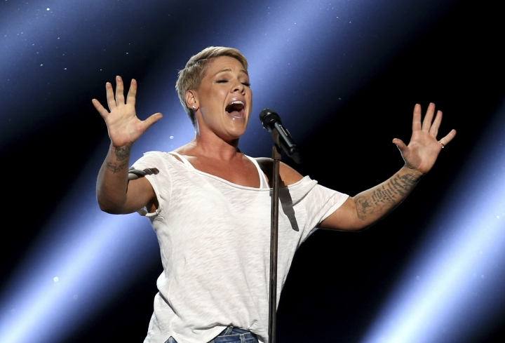 "FILE - In this Jan. 28, 2018, file photo, Pink performs ""Wild Hearts Can't Be Broken"" at the 60th annual Grammy Awards at Madison Square Garden in New York. Pink was admitted to a Sydney hospital on Monday, Aug. 6, with a virus, forcing her to postpone a second show, her promoter said. The singer's ""Beautiful Trauma"" world tour's first concert in Sydney was scheduled for last Friday, but she canceled that show on doctor's orders. She battled through a Saturday night show. (Photo by Matt Sayles/Invision/AP, File)"