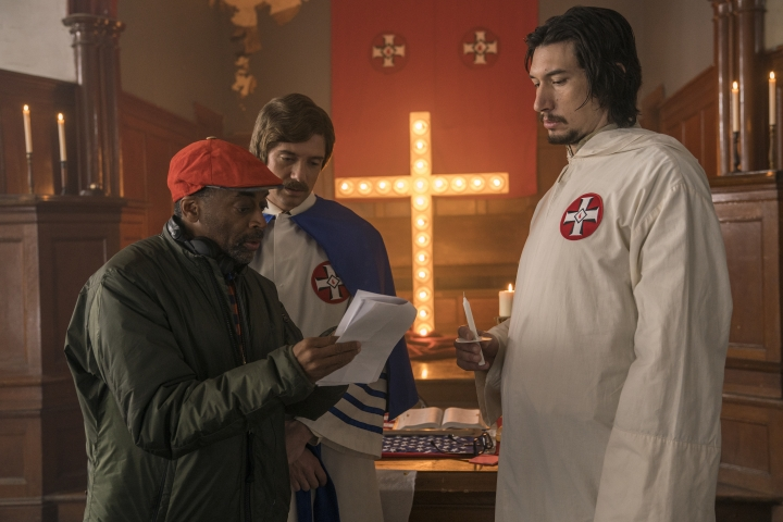 """This image released by Focus Features shows director Spike Lee, left, with actors Topher Grace, center, and Adam Driver on the set of Lee's film """"BlacKkKlansman."""" Lee is releasing his film this weekend, a year after the violent clashes in Charlottesville in which anti-racism activist Heather Heyer was run over and killed. Lee's film is about an earlier chapter in white supremacism and the Ku Klux Klan: when African-American police detective Ron Stallworth infiltrated a Colorado Springs, Colorado, chapter of the KKK in 1979. (David Lee/Focus Features via AP)"""