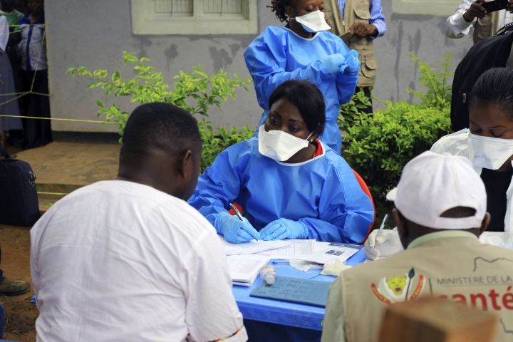 A healthcare worker from the World Health Organization prepares to give an Ebola vaccination to a front line aid worker in Mangina, Democratic Republic of Congo, Wednesday, Aug 8, 2018. Health experts began Ebola vaccinations in Congo's northeast village of Mangina for the latest deadly outbreak that has already claimed at least nine lives. (AP Photo/Al-hadji Kudra Maliro)