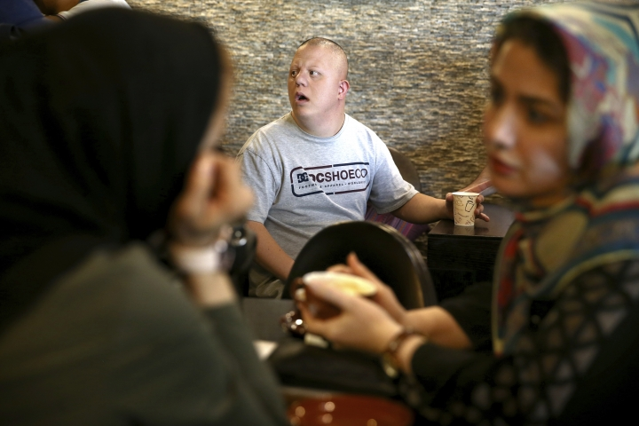 """In this Monday, Aug. 6, 2018, photo, cafe staff Ali Bakhti, 22, center, with down syndrome talks to his colleagues in Downtism Cafe in Tehran, Iran. The popular cafe, whose name combines """"Down"""" with """"autism,"""" in Tehran's bustling Vanak Square is entirely run by people with Down syndrome or autism. More than just providing meaningful work, the cafe is helping break down barriers by highlighting how capable people with disabilities are. (AP Photo/Ebrahim Noroozi)"""