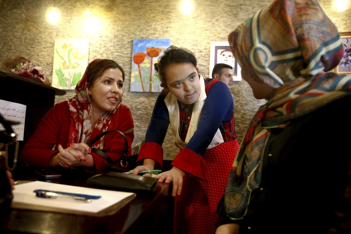 """In this Monday, Aug. 6, 2018, photo, cafe staff person Melika Aghaei, 14, center, with down syndrome takes an order in Downtism Cafe in Tehran, Iran. The popular cafe, whose name combines """"Down"""" with """"autism,"""" in Tehran's bustling Vanak Square is entirely run by people with Down syndrome or autism. More than just providing meaningful work, the cafe is helping break down barriers by highlighting how capable people with disabilities are. (AP Photo/Ebrahim Noroozi)"""