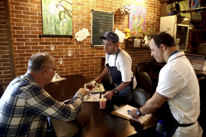 """In this Monday, Aug. 6, 2018, photo, two cafe staffers, Mehdi Khakian, with autism, center, and his colleague Iman Arbabi, with down syndrome, right, work in Downtism Cafe in Tehran, Iran. The popular cafe in Tehran's bustling Vanak Square, whose name combines """"Down"""" with """"autism,"""" is entirely run by people with Down syndrome or autism. More than just providing meaningful work, the cafe is helping break down barriers by highlighting how capable people with disabilities are. (AP Photo/Ebrahim Noroozi)"""