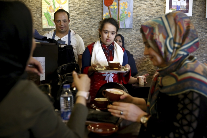 """In this Monday, Aug. 6, 2018, photo, cafe staff Melika Aghaei, 14, with down syndrome, center, works in Downtism Cafe in Tehran, Iran. The popular cafe, whose name combines """"Down"""" with """"autism,"""" in Tehran's bustling Vanak Square is entirely run by people with Down syndrome or autism. More than just providing meaningful work, the cafe is helping break down barriers by highlighting how capable people with disabilities are. (AP Photo/Ebrahim Noroozi)"""