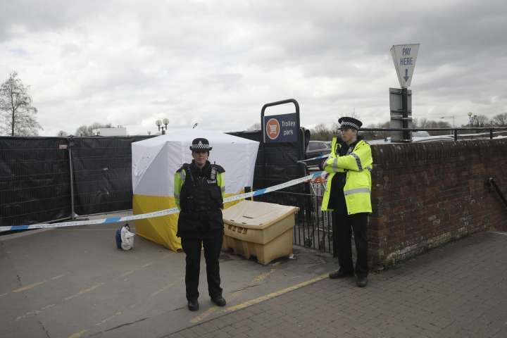 FILE - In this March 13, 2018, file photo, police officers guard a cordon around a police tent covering a supermarket car park pay machine near the spot where former Russian spy Sergei Skripal and his daughter were found critically ill following exposure to the Russian-developed nerve agent Novichok in Salisbury, England. The United States will impose sanctions on Russia for the country's use of a nerve agent in an assassination attempt on a former Russian spy and his daughter. The State Department says Aug. 8, sanctions will be imposed on Russia as the country used chemical or biological weapons in violation of international law.(AP Photo/Matt Dunham, File)