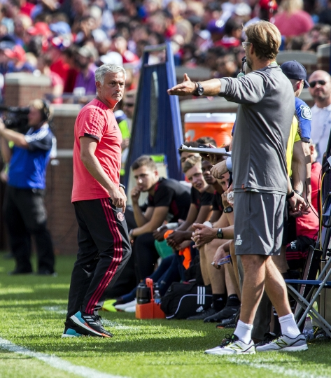 Manchester United manager Jose Mourinho, left, has an exchange on the touchline with Liverpool manager Jurgen Klopp, right, during the first half of an International Champions Cup tournament soccer match at Michigan Stadium, Saturday, July 28, 2018, in Ann Arbor, Mich. (AP Photo/Tony Ding)