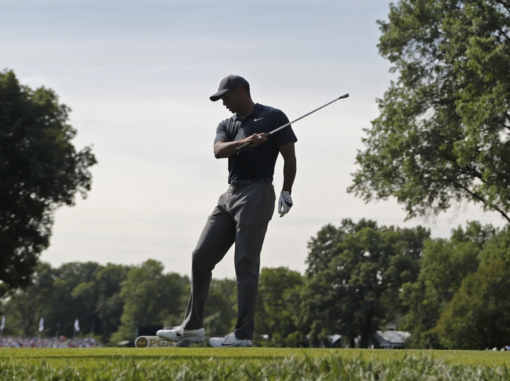 Tiger Woods reacts to his tee shot on the 16th hole during the first round of the PGA Championship golf tournament at Bellerive Country Club, Thursday, Aug. 9, 2018, in St. Louis. (AP Photo/Jeff Roberson)