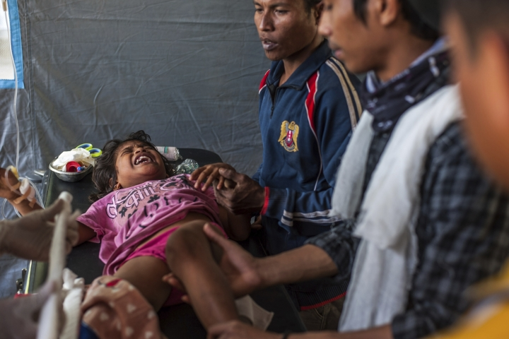 An Indonesian girl who was injured in Sunday's earthquake screams in pain as she is being treated at a makeshift hospital in Kayangan, North Lombok, Indonesia, Thursday, Aug. 9, 2018. Four days after the quake killed a large number of people of people and displaced hundreds of thousands more, injured survivors cut off by landslides, broken bridges and vast distances are still emerging from the countryside, struggling to reach the help they desperately need. (AP Photo/Fauzy Chaniago)