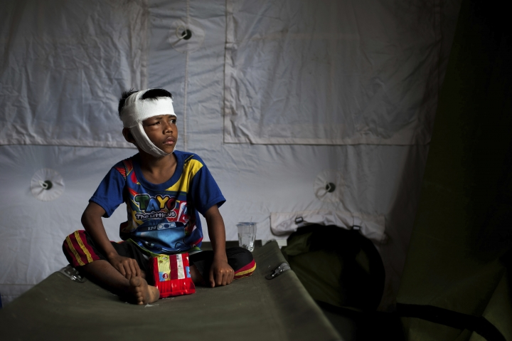 In this photo taken on Wednesday, Aug. 8, 2018, a boy who was injured in Sunday's earthquake sits on a folding bed at a makeshift hospital in Kayangan, North Lombok, Indonesia. Four days after the quake killed a large number of people of people and displaced hundreds of thousands more, injured survivors cut off by landslides, broken bridges and vast distances are still emerging from the countryside, struggling to reach the help they desperately need. (AP Photo/Fauzy Chaniago)