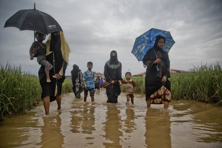 FILE - In this Nov. 17, 2017, file photo, Rohingya Muslims, who crossed over from Myanmar into Bangladesh, wade past a waterlogged path leading to the Jamtoli refugee camp in Ukhiya, Bangladesh. Myanmar on Thursday, Aug. 9, 2018, sharply rejected an attempt by the International Criminal Court to consider the country's culpability for activities that caused about 700,000 minority Rohingya Muslims to flee to Bangladesh for safety. The office of State Counsellor Aung San Suu Kyi, the country's leader, said in a statement posted online that the court in the Netherlands has no jurisdiction over Myanmar because it is not a member state. (AP Photo/A.M. Ahad, File)