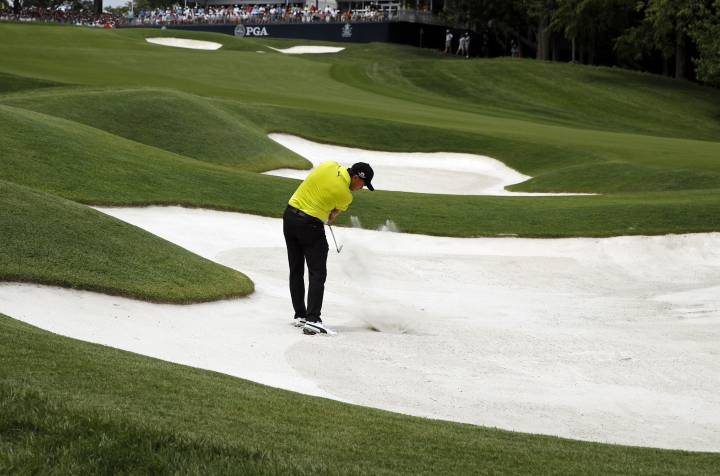 Rickie Fowler hits out of the bunker on the ninth hole during the first round of the PGA Championship golf tournament at Bellerive Country Club, Thursday, Aug. 9, 2018, in St. Louis. (AP Photo/Charlie Riedel)