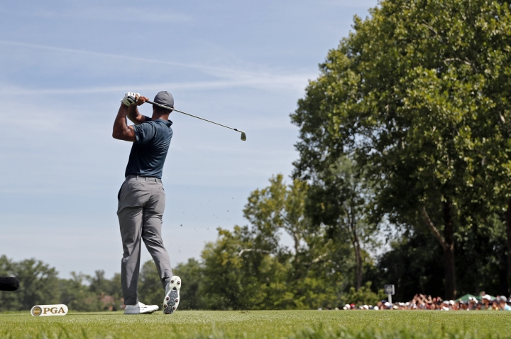 Tiger Woods watches his tee shot on the second hole during the first round of the PGA Championship golf tournament at Bellerive Country Club, Thursday, Aug. 9, 2018, in St. Louis. (AP Photo/Jeff Roberson)