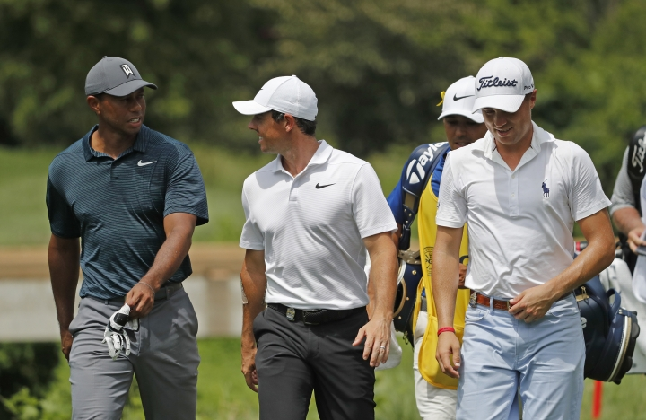Tiger Woods, left, Rory McIlroy, of Northern Ireland, center, and Justin Thomas, right, walk to the eighth fairway during the first round of the PGA Championship golf tournament at Bellerive Country Club, Thursday, Aug. 9, 2018, in St. Louis. (AP Photo/Jeff Roberson)