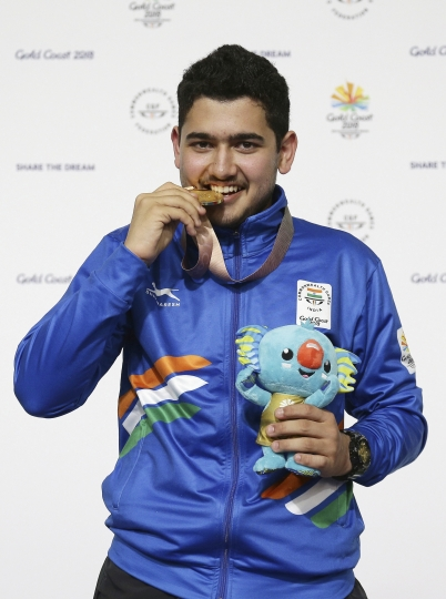 In this April 13, 2018, file photo, Anish Bhanwala of India celebrates with his gold medal at the men's 25m Rapid Fire Pistol final at the Belmont Shooting Centre during the 2018 Commonwealth Games in Brisbane, Australia. At 15 and still at high school, Anish was India's youngest gold medalist at the Commonwealth Games on Australia's Gold Coast in April when he won the 25-meter rapid fire pistol shooting event in a meet record. (AP Photo/Tertius Pickard, File)