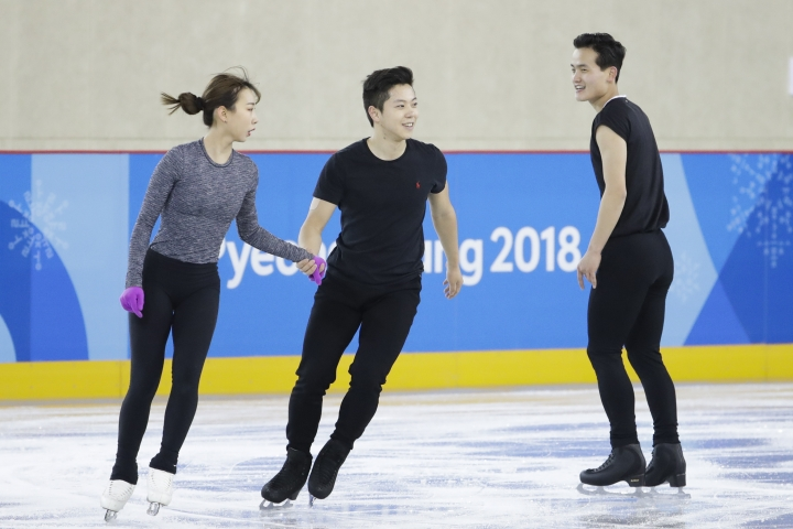 FILE - In this Feb. 5, 2018, file photo, North Korea's Kim Ju Sik, right, skates next to South Korea's Kim Kyueun, left, and Kam Alex Kang Chan during a Pairs Figure Skating training session prior to the 2018 Winter Olympics in Gangneung, South Korea. The war-separated rivals will take their reconciliation steps to the Asian Games in Jakarta and Palembang, Indonesia, where they will jointly march in the opening ceremony and field combined teams in basketball, rowing and canoeing. (AP Photo/Felipe Dana, File)