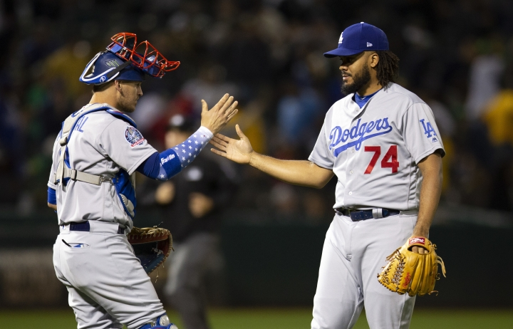 Los Angeles Dodgers catcher Yasmani Grandal (9) and pitcher Kenley Jansen (74) celebrate the team's 4-2 victory over the Oakland Athletics in a baseball game, Tuesday, Aug. 7, 2018, in Oakland, Calif. (AP Photo/D. Ross Cameron)