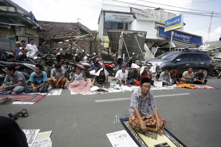 Villagers attend Muslim Friday prayer in front of the damage buildings in North Lombok, Indonesia, Friday, Aug. 10, 2018. The north of Lombok was devastated by the powerful quake that struck Sunday night, damaging thousands of buildings and killing a large number of people. (AP Photo/Firdia Lisnawati)