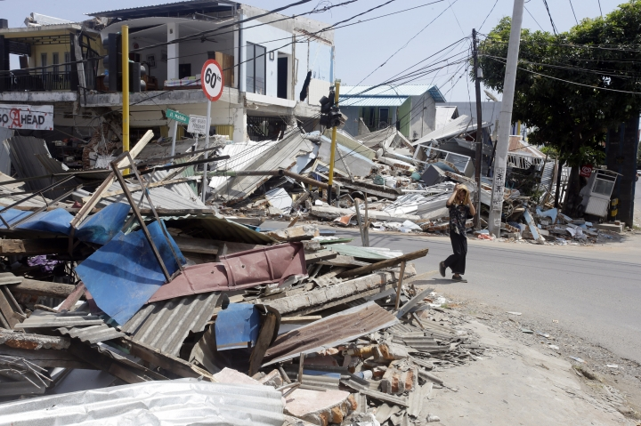 A man walks past destroyed buildings in North Lombok, Indonesia, Friday, Aug. 10, 2018. The north of Lombok was devastated by the powerful quake that struck Sunday night, damaging thousands of buildings and killing a large number of people. (AP Photo/Firdia Lisnawati)