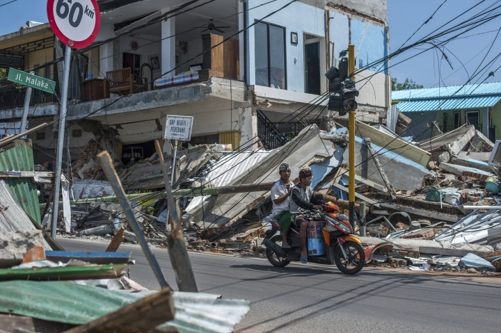 Motorists ride past buildings ruined by Sunday's earthquake in Pamenang, Lombok Island, Indonesia, Friday, Aug. 10, 2018. The north of the popular resort island has been devastated by Sunday's earthquake, damaging thousands of buildings and killing a large number of people. (AP Photo/Fauzy Chaniago)
