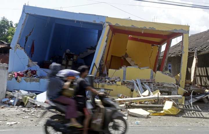 A motorcycle passes buildings destroyed by Sunday's earthquake in North Lombok, Indonesia, Friday, Aug. 10, 2018. The north of Lombok was devastated by the powerful quake that struck Sunday night, damaging thousands of buildings and killing a large number of people. (AP Photo/Firdia Lisnawati)