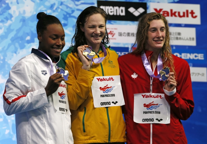Australia's Cate Campbell, center, poses with her medal on the podium after winning the women's 100m freestyle final with second-placed Simone Manuel, left of the U.S., and third-placed Ruck Taylor of Canada during the Pan Pacific swimming championships in Tokyo,Friday, Aug. 10, 2018. (AP Photo/Koji Sasahara)