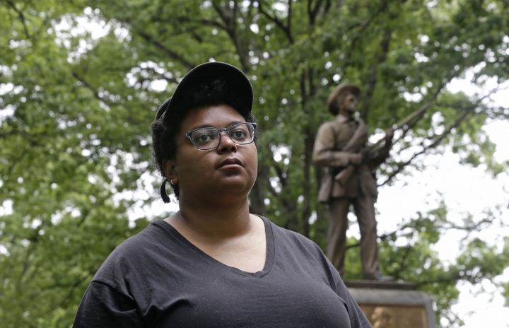 """Activist Maya Little stands near the """"Silent Sam"""" Confederate statue on campus at the University of North Carolina in Chapel Hill, N.C., on Tuesday, May 15, 2018. """"There is no Silent Sam without black blood, without violence towards black people,"""" the Ohio native said recently as she sat in the statue's shadow, campus security guards hovering behind nearby trees and columns. (AP Photo/Gerry Broome)"""
