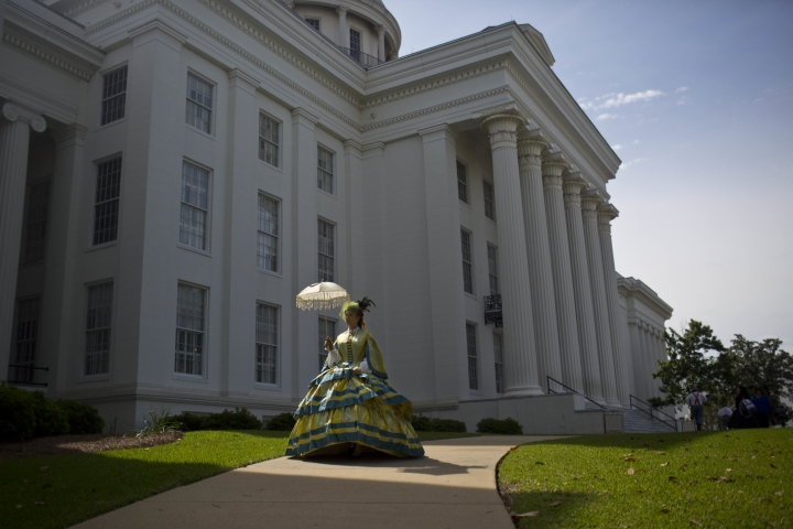 FILE - In this Monday, April 27, 2015 file photo, United Daughters of the Confederacy member Carrie McGough walks in front of the Alabama Capitol building during a confederate memorial day ceremony in Montgomery, Ala. McGough said she designed and sewed her hoop skirt to look like an authentic Civil War era dress. (AP Photo/Brynn Anderson)