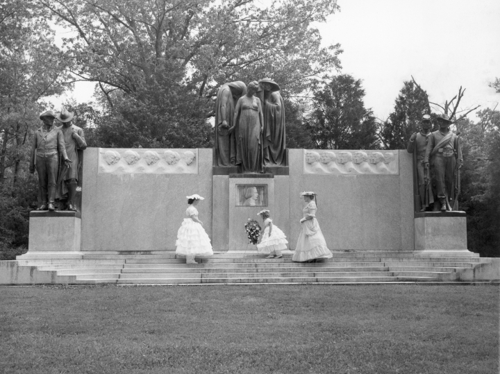 FILE - In this May 6, 1957 file photo, Mrs. Lonnie Holley, left, her 7-year-old daughter, Janalee, and Mrs. Benjamin T. Whitfield, dressed in Civil War-era clothing, place a wreath below the grieving women in the center of the monument honoring the Confederate dead at Shiloh, near Corinth, Miss. The monument was built by the United Daughters of the Confederacy. (AP Photo)