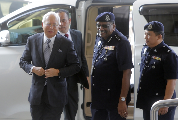 Malaysian former Prime Minister Najib Razak, left, arrives at High Court of Malaya in Kuala Lumpur, Malaysia, Friday, Aug. 10, 2018. Najib was charged of money laundering on Wednesday over a multibillion-dollar graft scandal at a state investment fund, the anti-corruption agency said. (AP Photo/Yam G-Jun)
