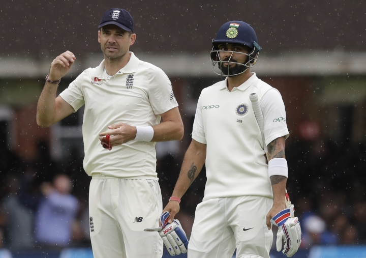 England's James Anderson, left, and India's captain Virat Kohli leaves the pitch as rain stops play during the second day of the second test match between England and India at Lord's cricket ground in London, Friday, Aug. 10, 2018. (AP Photo/Kirsty Wigglesworth)