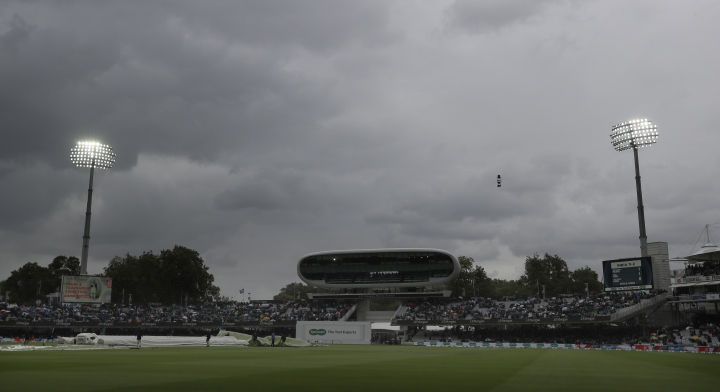 Rain covers are pulled onto the pitch as rain stops play during the second day of the second test match between England and India at Lord's cricket ground in London, Friday, Aug. 10, 2018. (AP Photo/Kirsty Wigglesworth)
