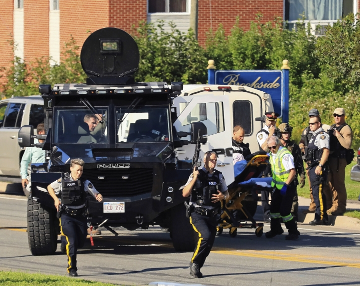 Police and RCMP officers survey the area of a shooting in Fredericton, New Brunswick, Canada on Friday, Aug. 10, 2018. Fredericton police say two officers were among four people who died in a shooting Friday in a residential area on the city's north side. One person was in custody, they said, and there was no further threat to the public. (Keith Minchin/The Canadian Press via AP)